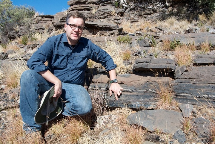 Study author Andrew Czaja shows the layer of rock from which fossil bacteria were collected in the Northern Cape Province of South Africa. Photo credits: Aaron Satkoski.